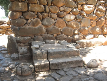 This is the base of a seat or throne for a city elder or the king in the city gate. Notice the four circular stones with a carved opening for a wooden post that would have supported a canopy over the ruler.